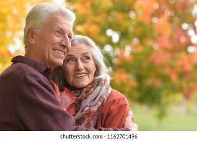 Portrait of happy Senior couple hugging in autumn park