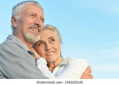 Portrait of happy senior couple hugging against blue sky