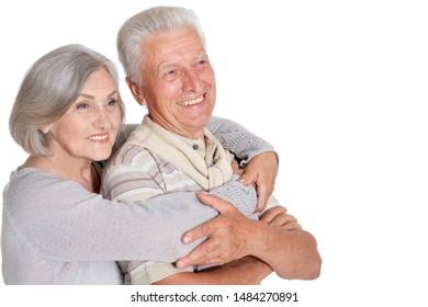 Portrait of happy senior couple hugging on white background