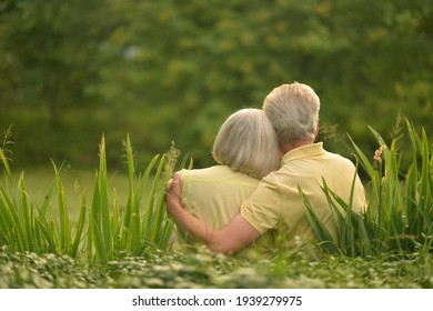 Portrait of happy senior couple near lake during sunset at summer