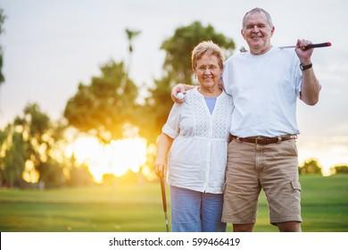 portrait of happy senior couple playing golf enjoying retirement