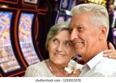 Portrait of happy senior couple posing on blurred casino hall background