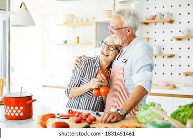 Portrait of happy senior couple prepering meal in kitchen