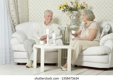 Portrait of happy senior couple resting at home with tea cups