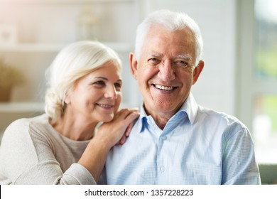Portrait of happy senior couple sitting on sofa at home