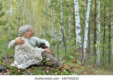 Portrait of happy senior couple sitting on lawn in autumn birch forest