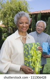 Portrait of happy senior couple standing together while holding gift boxes