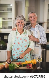 Portrait of happy senior couple standing together in kitchen at home
