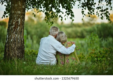 Portrait of happy senior couple taking rest outdoors