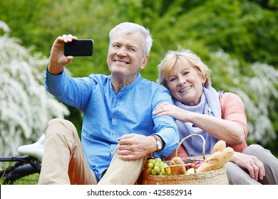 Portrait of happy senior couple taking selfies with smart phone while picnic and relaxing outdoor.