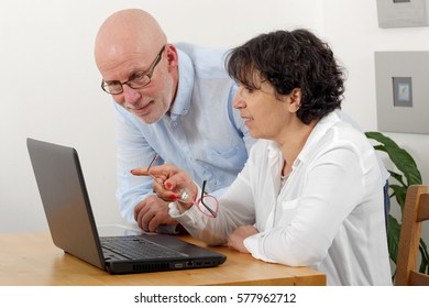 Portrait of a happy senior couple using laptop at home