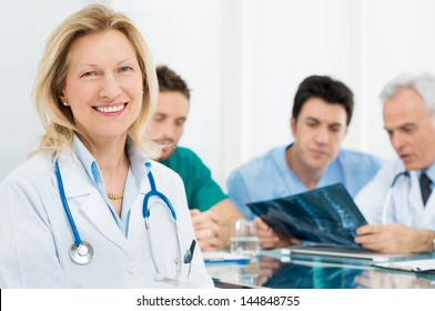 Portrait Of Happy Senior Female Doctor With Her Team