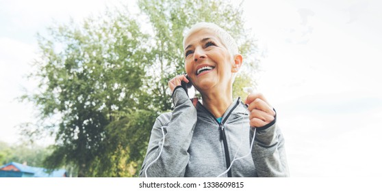 Portrait Of Happy Senior Fitness Woman With Earphones , Wear Sports Clothes , Short Hair