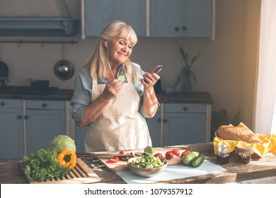 Portrait of happy senior lady listening to music from headphones while cooking in kitchen. She is looking at mobile phone and smiling while eating cucumber slice