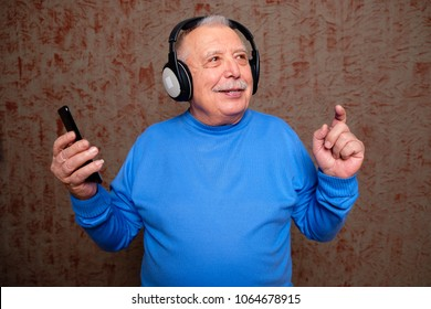 Portrait of Happy senior man 70-75 years old listening music in headphone and hold smartphone in hand on background
