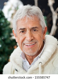 Portrait of happy senior man in Christmas store