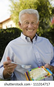 Portrait of happy senior man eating piece of cake at party