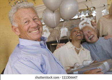 Portrait of happy senior man holding gift with friends laughing in the background