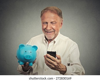 Portrait happy senior man holding piggy bank looking at smart phone isolated grey background. Financial savings banking concept, customer satisfaction contract agreement. Positive face expression