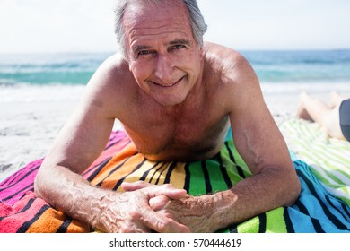 Portrait of happy senior man lying on the beach on a sunny day