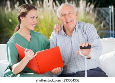 Portrait of happy senior man sitting by female nurse holding book at nursing home