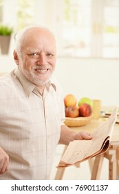 Portrait of happy senior man sitting at breakfast table, holding newspaper, smiling at camera.?