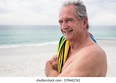 Portrait of happy senior man standing on beach with towel on shoulder