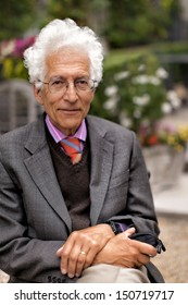 Portrait of a happy senior man with white hair wearing a pink shirt with a tie and jacket, sitting outside in a garden. Shot with shallow dof.