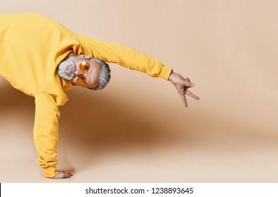 Portrait of happy senior millionaire man show peace sign in yellow sunglasses stylish fashionable men senior on beige background