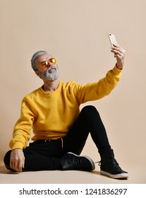 Portrait of happy senior millionaire man using smartphone cellphone make selfie in yellow sunglasses stylish fashionable men senior looking at camera