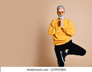 Portrait of happy senior millionaire man in yellow sunglasses stylish fashionable men practicing yoga asana stretching exercise on beige background