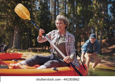 Portrait of happy senior paddling kayak in the lake with man supporting from behind. Mature couple enjoying a day at the lake.