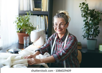 Portrait of happy senior seamstress wearing plaid shirt and glasses sitting at desk in front of sewing machine, working on wedding dress at home. People, age, job, occupation and profession concept