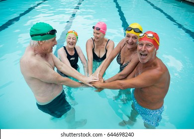Portrait of happy senior swimmer stacking hands in pool