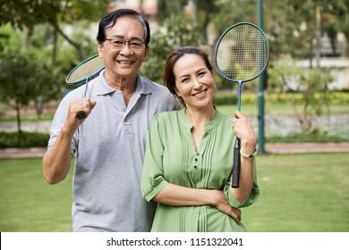 Portrait of happy senior Vietnamese couple with badminton racquets