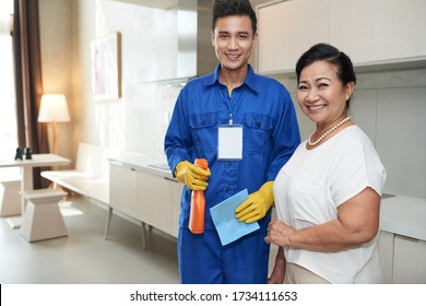 Portrait of happy senior Vietnamese woman and cleaning service worker holding detergent with cellulose sponge
