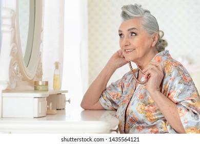 Portrait of happy senior woman applying makeup