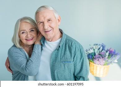 portrait of happy senior woman bonding to husband isolated on grey