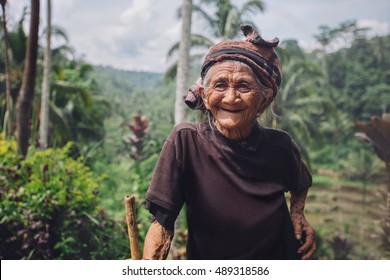 Portrait of happy senior woman with a cane in village. Smiling old female outdoors in countryside.