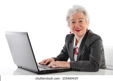 Portrait of happy senior woman with computer - isolated on white.