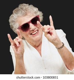 portrait of a happy senior woman doing a rock symbol over a black background
