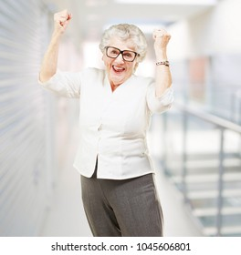 portrait of a happy senior woman doing a victory gesture indoor