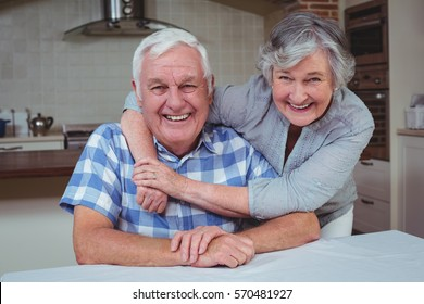Portrait of happy senior woman embracing man from behind in kitchen
