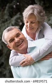 Portrait of a happy senior woman embracing her husband