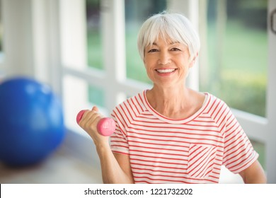 Portrait of happy senior woman exercising with dumbbell at home