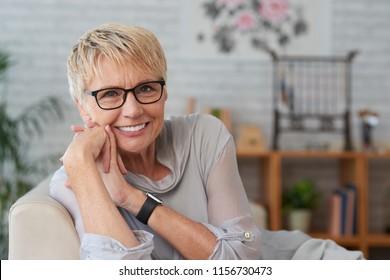 Portrait of happy senior woman in glasses resting on sofa