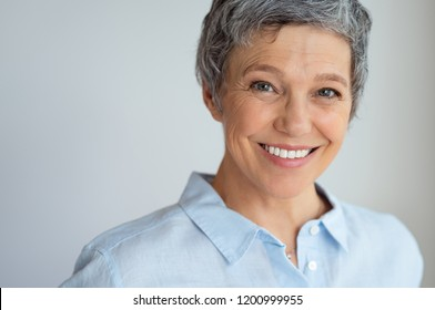 Portrait of happy senior woman isolated against gray background with copy space. Closeup face of confident business woman smiling. Successful businesswoman with a friendly smile looking at camera.