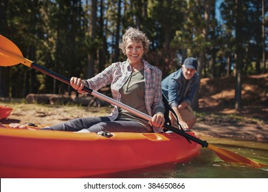 Portrait of happy senior woman in a kayak holding paddles. Woman canoeing with man in background on the lake.