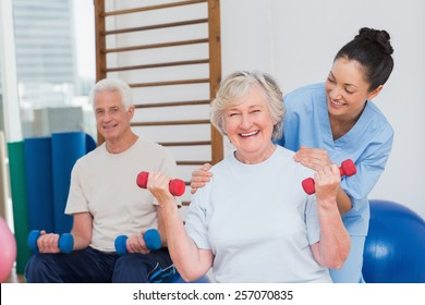 Portrait of happy senior woman lifting dumbbells while sitting with man and trainer in gym