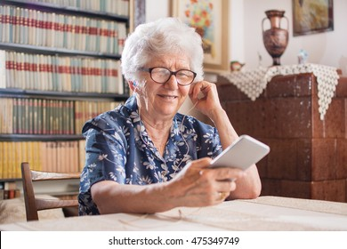 Portrait of a happy senior woman listening to music on smartphone at home.